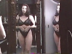 Mimi Rogers standing in front of a mirror in a black br...
