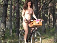 Naked college cutie rides a bike in the woods