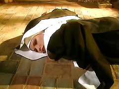 Michelle Thorne lying on the ground in a nun's outfit a...