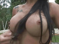Foxy brunette shemale jerking her cock outdoors