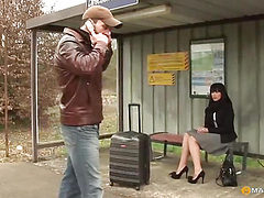 Kisses his girlfriend sitting at the bus stop
